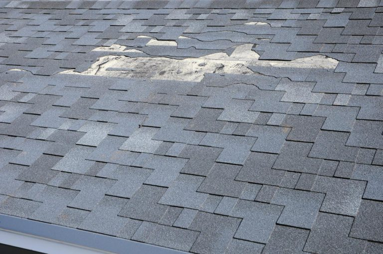 Roof damage insurance claims restoration by Columbus roofing company near me needed due to broken, old, and missing shingles on this house roof.