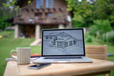 Columbus, Ohio new home builders and construction services blueprint on laptop in front of house